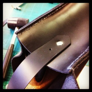 attaching the strap with metal rivets...